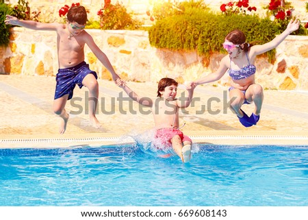 Happy Children In The Pool Three Active Friends With Pleasure Jumping Tho Water