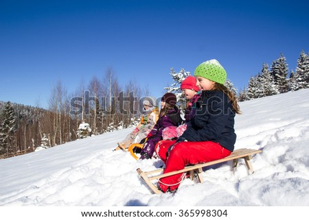 Happy children in winter. Children playing on the snow. Children sledging