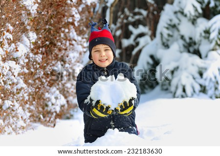 Happy children in winterwear laughing while playing in snowdrift outside  - stock photo