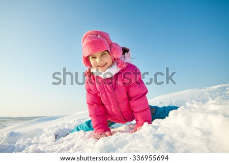 Happy children in winterwear laughing while playing in snowdrift outside