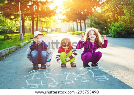 Happy children is drawing on asphalt in spring park. Background toning for instagram filter. - stock photo