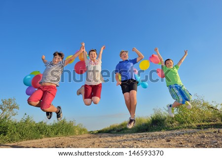 happy children jumping on field with balloons in summer time  - stock photo