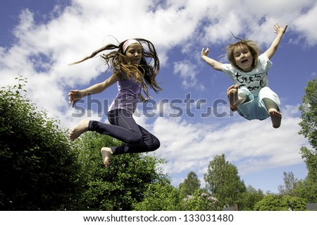 Happy children jumping on trampoline - stock photo