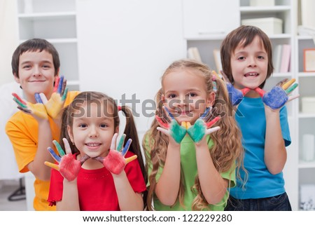 Happy children keeping their colored hands at chins