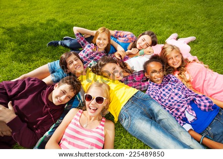 Happy children laying together on green grass - stock photo