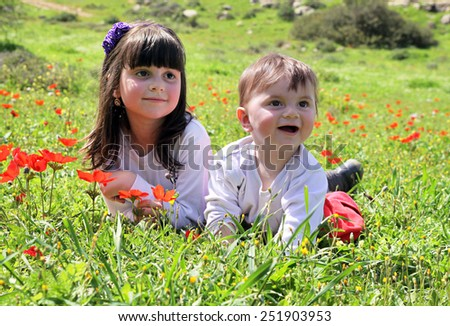 Happy children lie on a meadow among the flowers