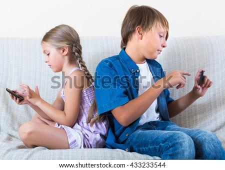 Happy children looking at screen of modern smartphones indoors - stock photo
