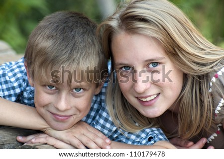 Happy children lying on green grass outdoors in the park