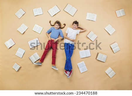 Happy children lying on the floor with group of books - stock photo