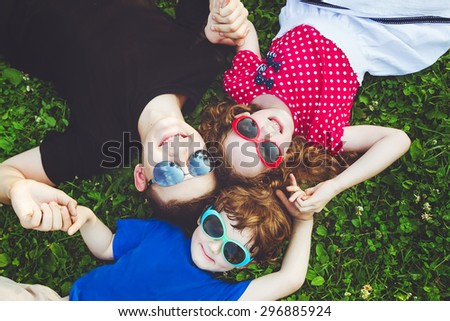 Happy children lying on the grass holding hands. Top view. - stock photo