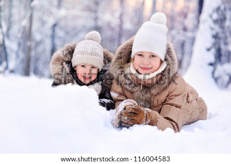 happy children lying on the snow in winter