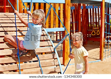 Happy children move out to slide in playground. - stock photo