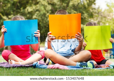 Happy children of three sitting on grass with books - stock photo