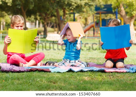 Happy children of three sitting with books - stock photo