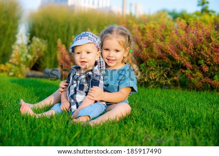 Happy children on green grass in spring park. Healthy lifestyles concept. - stock photo
