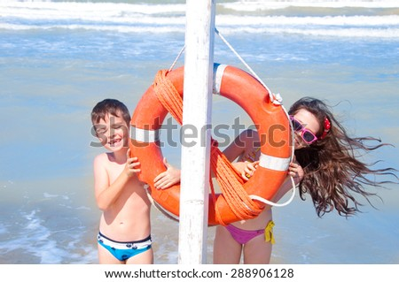 Happy children on the beach playing with lifebuoy - stock photo