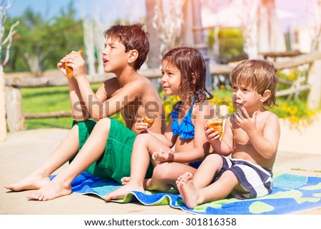 Happy children on the beach, three little best friends resting near the pool and eating croissants, enjoying active summer holidays - stock photo