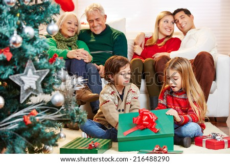 Happy children opening gifts at christmas while parents and grandparents are watching - stock photo