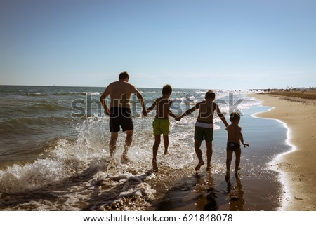 Happy children playing and splashing in the sea beach. Kids having fun outdoors. Summer vacation and healthy lifestyle concept.