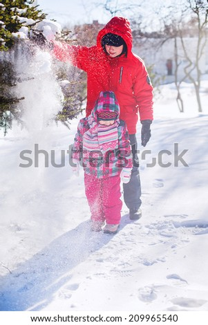 happy children playing in a winter park. snow, sunny winter day - stock photo