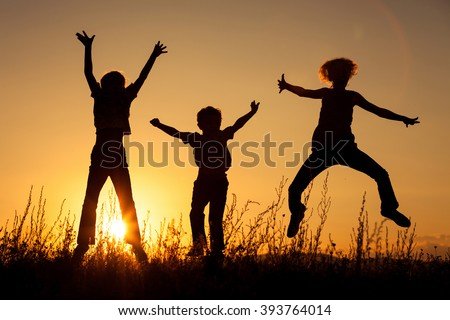 Happy children playing in the park at the sunset time. Concept of friendly family.