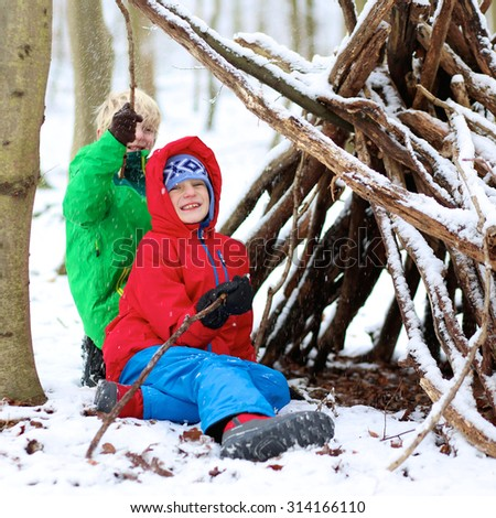 Happy children playing in winter forest. Kids enjoying snow building tent from trees branches. Healthy teenage boys having active snowy holidays. - stock photo