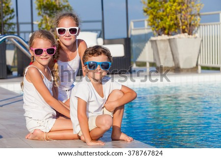 happy children  playing near the swimming pool at the day time. Concept of friendly family. - stock photo