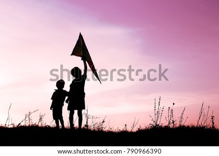 Happy children playing on nature summer silhouette