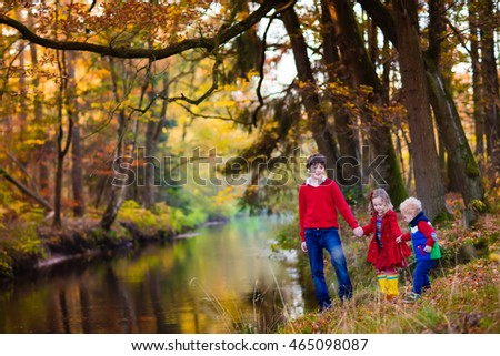 Happy children playing on river shore in beautiful autumn park on warm sunny fall day. Kids play with golden maple leaves.