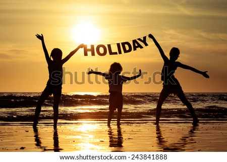 "Happy children playing on the beach at the sunset time. Children hold in the hands  inscription ""Holiday"""