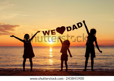 "Happy children playing on the beach at the sunset time. Children hold in the hands  inscription ""We love dad"". Concept of happy father day."
