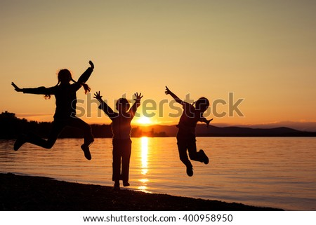 Happy children playing on the beach of lake at the sunset time. Concept of happy friendly sister and brother. - stock photo
