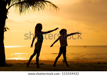 Happy children playing on the beach on the dawn time