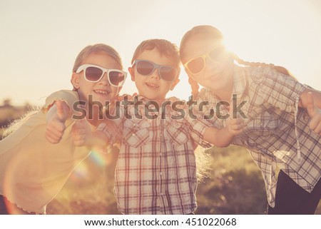 Happy children playing on the field at the day time. Concept of friendly siblings of family.