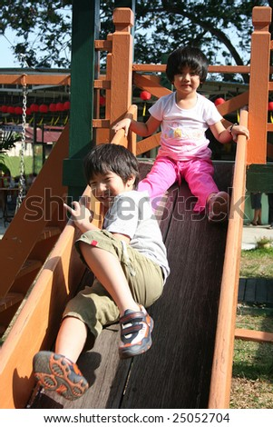 Happy children playing slide at the playground in the park on sunny day