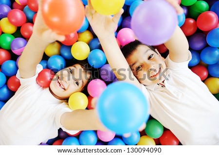 Happy children playing together and having fun at kindergarten with colorful balls - stock photo