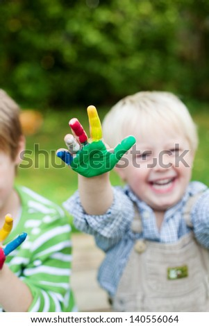 Happy children playing with colorful hands outdoors - stock photo