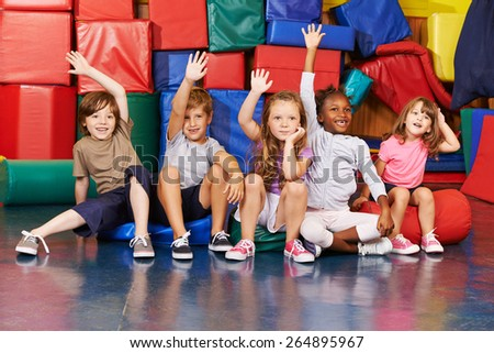 Happy children raising their hands in gym of an elementary school