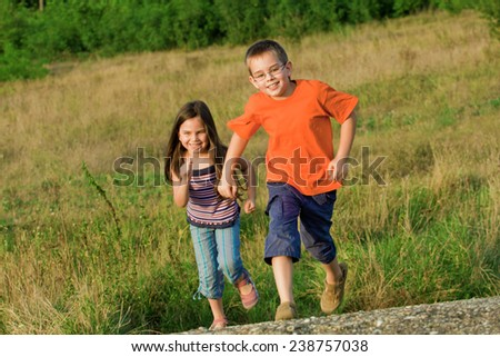 Happy children running at meadow, in motion - stock photo