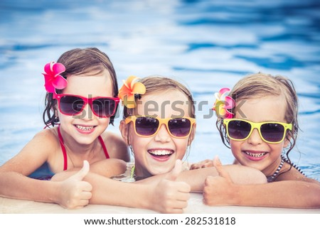 Happy children showing thumbs up in the swimming pool. Funny kids playing outdoors. Summer vacation concept - stock photo