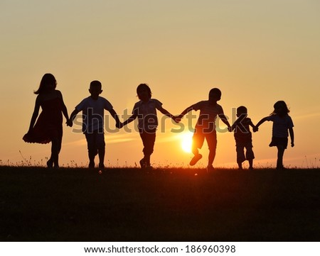 People Silhouettes On Sunset Meadow Having Stock Photo ...