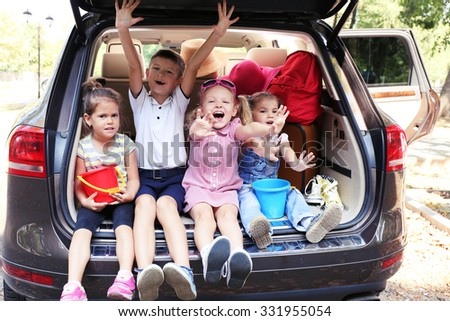 Happy children sit on a car trunk and laughing - stock photo
