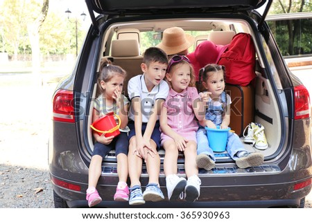Happy children sit on a car trunk and laughing