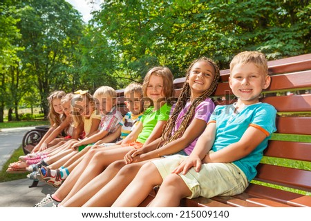 Happy children sit on the bench in park
