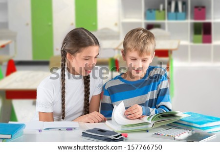 Happy children sitting by the table and reading a book - stock photo