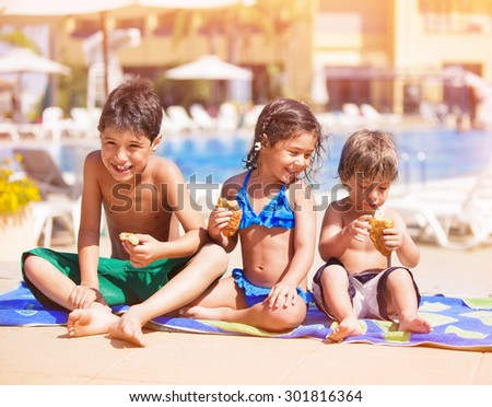 Happy children sitting near the pool and eating croissants, having break after swimming, two cheerful brother and cute sister enjoying summer vacation on beach resort - stock photo