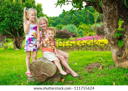 happy children sitting on a bench near the tree
