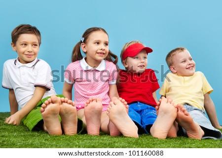 Happy children sitting on the grass barefoot - stock photo