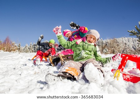 Happy children sledding at winter time. Group of children spending a nice time in winter. - stock photo