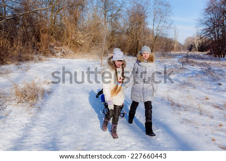 Happy children sledding in the winter forest. Christmas